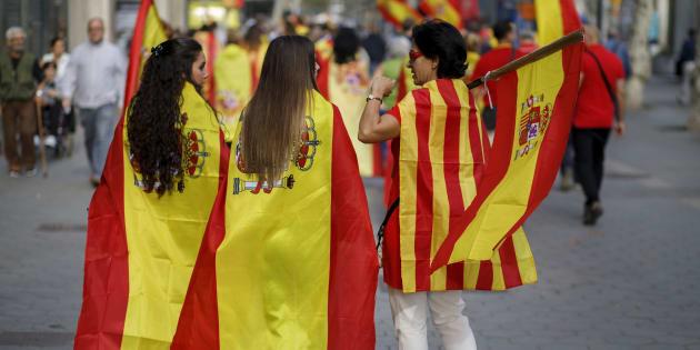Pessoas usando as bandeiras da Espanha e da Catalunha andam juntas.