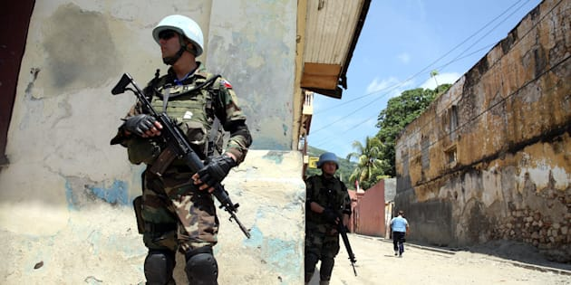 CAP-HAITIEN, HAITI - JULY 30:  U.N. Peacekeepers patrol outside a government building that was seized by former soldiers of the Armed Forces of Haiti July 30, 2008 in Cap-Haitien, Haiti.  About 200 ex-soldiers, some wearing camouflage and armed, occupied the buildings which were the former army headquarters and prison in the northern city of Cap-Haitien and an army barracks in Ouanaminthe. They are demanding 14 years of back-pay and reinstatement of the country's armed forces which was disbanded in 1995 by ousted president, Jean-Bertrand Aristide. U.N. peacekeepers and Haitian police were dispatched to negotiate a peaceful surrender.  (Photo by Daniel Morel/Getty Images)