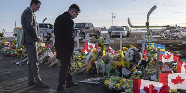 A group of Saskatchewan Junior Hockey League referees look at a memorial at the intersection of a fatal bus crash that killed 16 members of the Humboldt Broncos hockey team near Tisdale, Sask. on April 14, 2018.