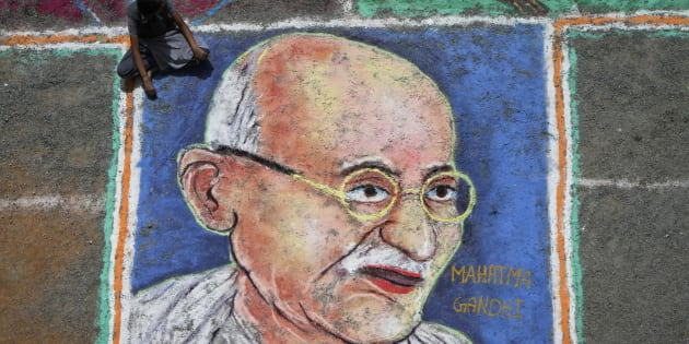 A student sits next to a painting of Mahatma Gandhi as part of Independence Day celebrations.