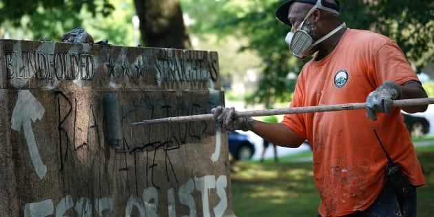 """Un employé de la ville de Baltimore (Maryland) retire des graffitis des statues de Robert E. Lee et Thomas """"Stonewall"""" Jackson, deux figures de l'armée confédérée durant la guerre de Sécession"""