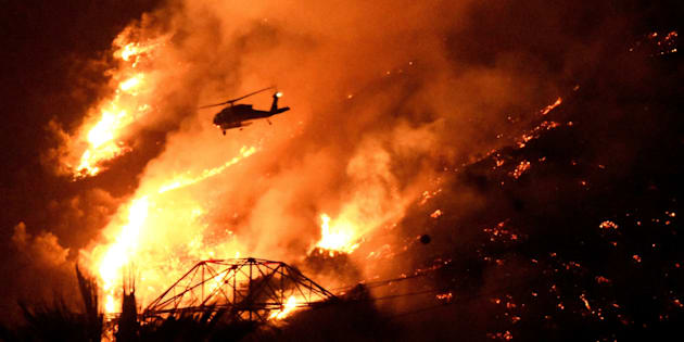 A Los Angeles County fire helicopter makes a night drop while battling the so-called Fish Fire above Azusa, California, U.S. June 20, 2016.  REUTERS/Gene Blevins