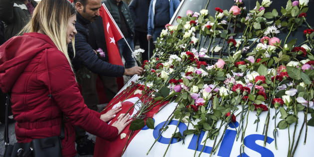 Une femme pleure devant un fourgon de police couvert de fleurs, lors d'un hommage aux victimes de l'attentat devant la Vodafone Arena, le 11 décembre 2016.