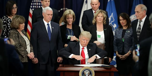 WASHINGTON, DC - JANUARY 25:  (AFP-OUT) U.S. President Donald Trump (C) signs four executive orders during a visit to the Department of Homeland Security with Vice President Mike Pence, Homeland Security Secretary John Kelly and other officials January 25, 2017 in Washington, DC. Trump signed four executive orders related to domestic security and to begin the process of building a wall along the U.S.-Mexico border.  (Photo by Chip Somodevilla/Getty Images)