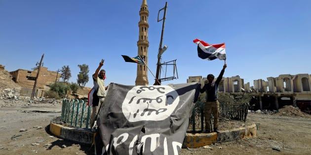 Des membres des Unités de mobilisation populaire descendent le drapeau de Daech dans la ville de Tal Afar en Irak, en août 2017.