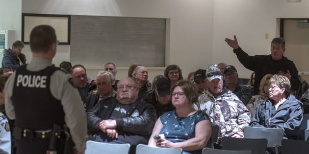 Gerry Besse, a resident of Biggar, Sask. asks RCMP Commander Colin Sawrenko a question during an RCMP town hall on Monday.