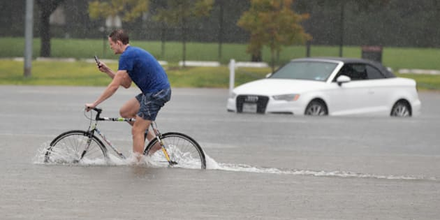 HOUSTON, TX - AUGUST 27:  Cade Ritter rides through a flooded parking lot on the campus of Rice University afer it was inundated with water from Hurricane Harvey on August 27, 2017 in Houston, Texas. Harvey, which made landfall north of Corpus Christi late Friday evening, is expected to dump upwards to 40 inches of rain in areas of Texas over the next couple of days.  (Photo by Scott Olson/Getty Images)