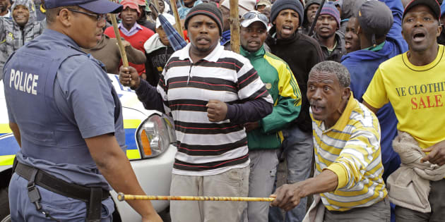 A South African policeman, left,  provide security as farm workers demonstrate due to low wages in the town of Grabouw, South Africa, Wednesday, Jan 9, 2013.