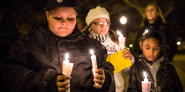 NEW YORK, NY - OCTOBER 29:  Damion Antonetty (L), a resident of the Red Hook neighborhood of Brooklyn, participates in a moment of silence during a candle light vigil to commemorate the one year anniversary of Superstorm Sandy hitting New York, on October 29, 2013 in Red Hook neighborhood of the Brooklyn borough of New York City.