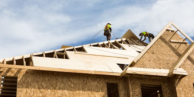 Workers build the roof of a house under construction in Brampton, Ont., Sat. May 20, 2017. Buyers in Canada's most overheated real estate markets paid an average of $229,000 extra per home between 2007 and 2016 because of regulations making it difficult for builders to construct more single-family houses, said a new study.
