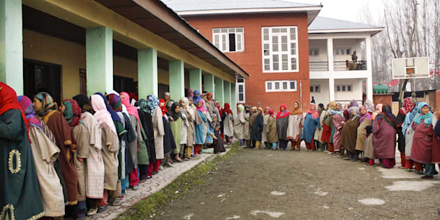 Kashmiri women stand in a queue to cast their votes.