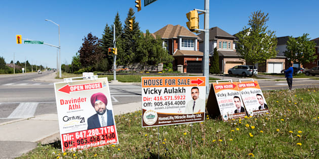 Open house signs are displayed on the side of a road in the Toronto suburb of Brampton, Sat. May 20, 2017. The city's housing market slowed sharply last spring in the wake of a foreign buyer's tax, and could feel more pressure this year with tougher new mortgage rules in place.