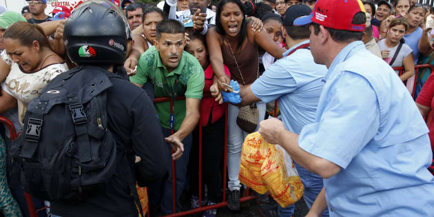People attempt to buy chickens at a Mega-Mercal, a subsidized state-run street market, in Caracas January 24, 2015. President Nicolas Maduro shook up complex currency controls on Wednesday and also prepared Venezuelans for a rise in the world's cheapest fuel prices in response to a recession worsened by plunging oil revenue. The socialist-run OPEC member's economy shrank 2.8 percent in 2014 while inflation topped 64 percent, the socialist leader announced in a speech to parliament, in what is almost certainly the worst performance in Latin America.  REUTERS/Carlos Garcia Rawlins (VENEZUELA - Tags: BUSINESS POLITICS FOOD SOCIETY)
