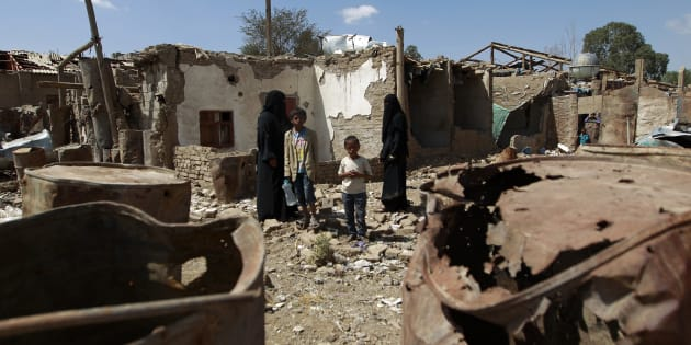 Yemeni family members stand outside their house which was damaged several months ago in an air strike by the Saudi-led coalition at a slum in the capital Sanaa, on March 12, 2016.