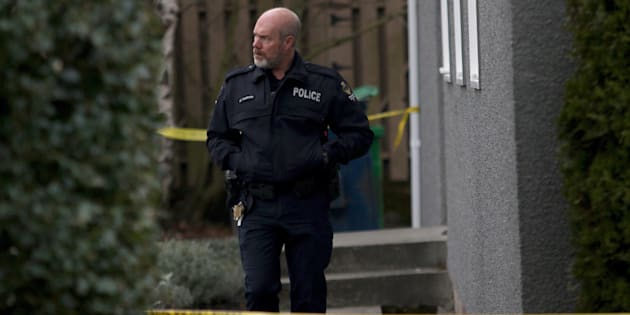 An Oak Bay officer leaves the apartment building where the bodies of sisters aged four and six were found by police on Boxing Day in the community of Oak Bay in Victoria, B.C., on Wednesday.
