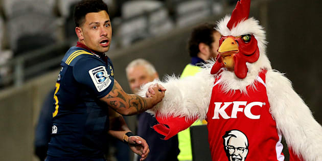 The Highlanders' Rob Thompson celebrates his try with the KFC mascot in a Super Rugby Match in Dunedin.