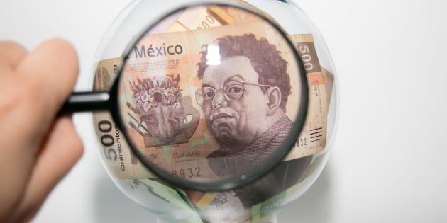 Dinero mexicano, 500 pesos, dentro de una esfera siendo inspeccionado por una lupa