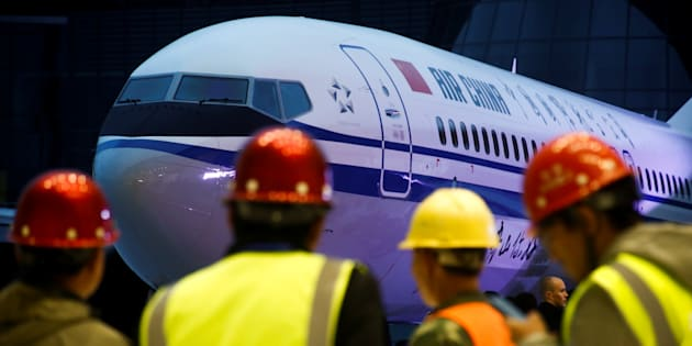 Workers attend a ceremony marking the first delivery of a Boeing 737 Max 8 airplane to Air China in Zhoushan, Zhejiang province, China, Dec. 15, 2018.
