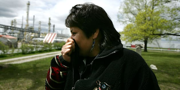 Aamjiwnaang activist Ada Lockridge holds her nose as intense odors pass through the native burial grounds on the reserve across from Suncorp Energy Corporation, Inc. in Sarnia, Ont. in 2008.