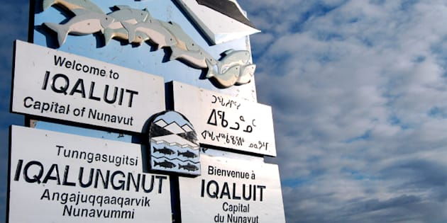 A sign written in various languages, clockwise from top left, English, Inuktitut (syllabic), French, and Inuktikut (Roman orthography), welcomes visitors to Iqaluit on Aug. 16, 2007.