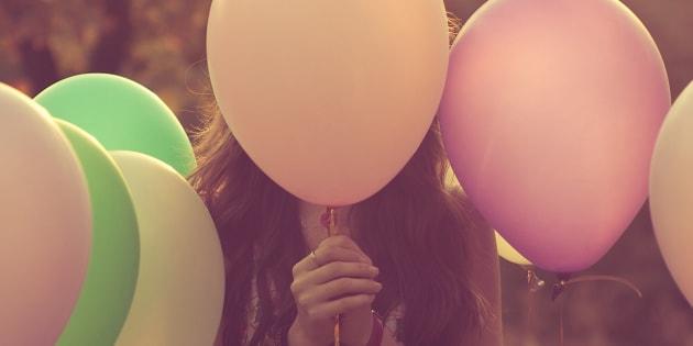 Girl hiding behind balloons.