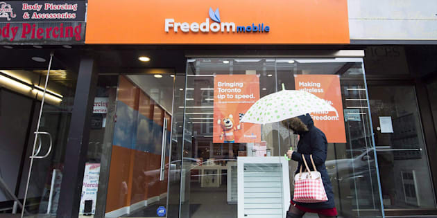 A woman walks past the rebranded signage of Freedom Mobile, in Toronto on Nov. 24, 2016. Freedom Mobile's new wireless plans include 10 GB of data for $50.