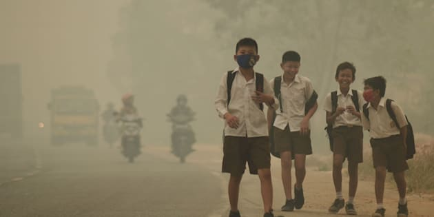 """Students walk along a street as they are released from school to return home earlier due to the haze in Jambi, Indonesia's Jambi province, September 29, 2015 in this picture taken by Antara Foto. Indonesia has sent nearly 21,000 personnel to fight forest fires raging in its northern islands, the disaster management agency said on Tuesday, but smoke cloaks much of the region with pollution readings in the """"very unhealthy"""" region in neighboring Singapore.   REUTERS/Antara Foto/Wahdi Setiawan       ATTENTION EDITORS - THIS IMAGE HAS BEEN SUPPLIED BY A THIRD PARTY. IT IS DISTRIBUTED, EXACTLY AS RECEIVED BY REUTERS, AS A SERVICE TO CLIENTS. FOR EDITORIAL USE ONLY. NOT FOR SALE FOR MARKETING OR ADVERTISING CAMPAIGNS. MANDATORY CREDIT. INDONESIA OUT. NO COMMERCIAL OR EDITORIAL SALES IN INDONESIA."""