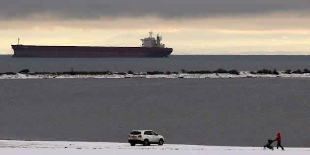 An oil tanker anchors in Strait of Juan de Fuca as a man walks to his car along the grounds of Royal Roads University looking towards Esquimalt Lagoon following snowfall in Victoria, Dec. 9, 2016.