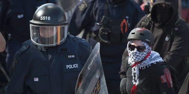 Des manifestants aux côtés de la police lors d'un rassemblement pacifique à Québec, le 9 juin 2018.