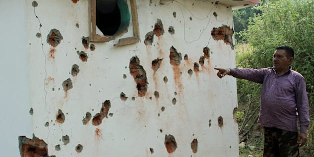 Jammu: A villagers  points out damaged wall of a house after mortal shelling from Pakistan, at Jhanghar village area near the Line of Control (LoC) at Nowshera sector 145km about from Jammu on Sunday. PTI Photo