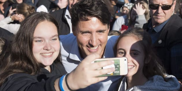 Prime Minister Justin Trudeau gets a self taken with young women at a picnic in Rouyn-Noranda, Que., on Aug. 15, 2018.