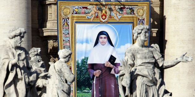 A tapestry depicting Sister Alphonsa of the Immaculate Conception is seen among the statues of St. Peter's Colonnade during the canonisation ceremony led by Pope Benedict XVI  in St. Peter square at the Vatican October 12, 2008. REUTERS/Alessandro Bianchi   (VATICAN)