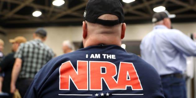 Un asistente a una reunión anual de la NRA muestra orgulloso su playera de miembro de la polémica organización.