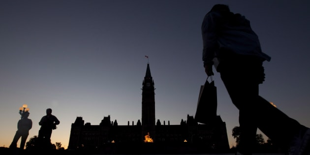 Visitors come and go as the Parliament Buildings are silhouetted at dusk on June 13, 2012.