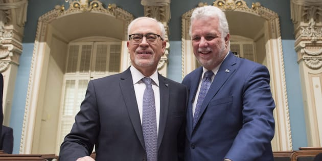 Quebec Finance Minister Carlos Leitao is joined by Premier Philippe Couillard, as he arrives to table his budget on March 27, 2018 at the National Assembly in Quebec City. The budget includes a measure to tax Netflix and other foreign online businesses.