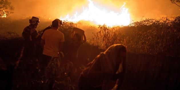 Unos vecinos observan cómo se acerca a sus casas el incendio forestal de Carballeda de Avia (Ourense).