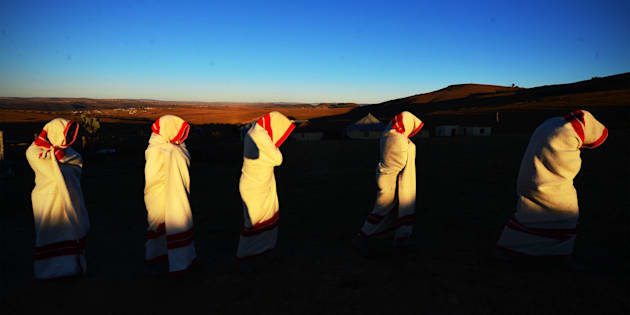 Initiates are smeared with white clay on their face and are covered in red and white blankets on June 20, 2014 in Ngunjana Village, South Africa.