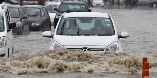 SRINAGAR, INDIA - APRIL 6: Vehicles navigate their way through a waterlogged street after fresh snowfall  on April 6, 2017 in Srinagar, India.