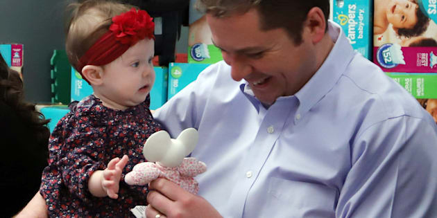 Conservative Party Leader Andrew Scheer plays with 8 month old Ruth Toews prior to announcing that he is putting forward a private members bill to introduce a tax break for new parents in Ottawa, Feb. 1, 2018.