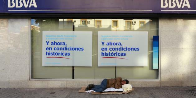 Un hombre sin hogar duerme a las puertas de un banco, en Sevilla.