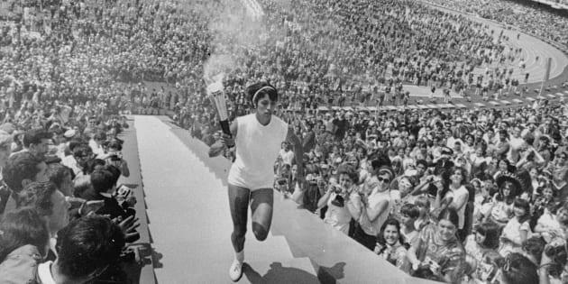 Enriqueta Basilio lleva la antorcha olímpica por los 90 escalones hasta el caldero de la llama olímpica durante las ceremonias de inauguración de los Juegos Olímpicos en Ciudad de México el 12 de octubre de 1968. El fondo es parte del vasto Estadio Olímpico. Enriqueta fue la primera mujer en hacer la carrera final de la antorcha y encender la llama olímpica.