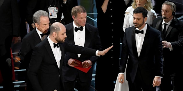 HOLLYWOOD, CA - FEBRUARY 26:  'La La Land' producer Jordan Horowitz (C) stops the show to announce the actual Best Picture winner as 'Moonlight' following a presentation error with actor Warren Beatty (L) and host Jimmy Kimmel (R) onstage during the 89th Annual Academy Awards at Hollywood & Highland Center on February 26, 2017 in Hollywood, California.  (Photo by Kevin Winter/Getty Images)