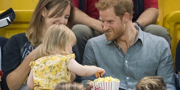 Prince Harry sits with Hayley Henson, left, and her daughter Emily Henson at the Invictus Games in Toronto on Sept. 27, 2017 in Toronto.