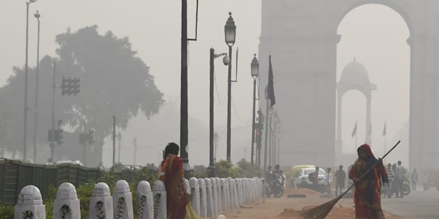A sweeper cleans a road amid heavy smog near India Gate in New Delhi on November 16, 2017.