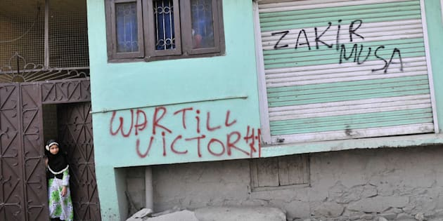 SRINAGAR, INDIA - JULY 8: Kashmiri children stand next to graffiti that reads War till Victory and a militant commander Zakir Musa during curfew in Lal Chowk area, on July 8, 2017 in Srinagar, India.