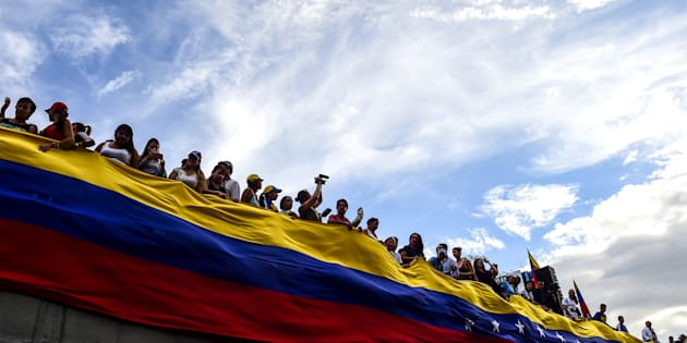 Opposition activists hold a large Venezuelan flag during a protest in Caracas, on July 24, 2017.