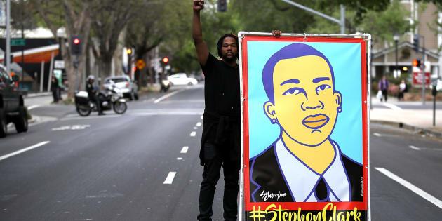 Sacramento (California, EEUU), 4 de abril. Un manifestante sostiene una ilustración de Stephon Clark durante una protesta para pedir justicia por su muerte. Clark, un joven negro de 22 años, fue disparado por un policía el 18 de marzo.