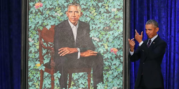 Former U.S. president Barack Obama stands next to his newly unveiled portrait.