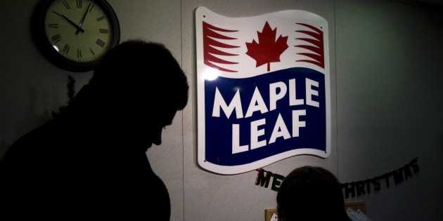 A Maple Leaf Foods employee and a representative of the media at the company's meat facility in Toronto, Mon. Dec. 15, 2008.