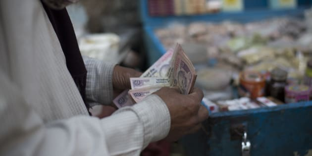 A man counts Indian rupee notes in Kolkata, India, on Tuesday, Feb. 19, 2013. India's slowest economic expansion in a decade is limiting profit growth at the biggest companies even as foreigners remain net buyers of the nation's stocks, according to Kotak Institutional Equities. Photographer: Brent Lewin/Bloomberg via Getty Images